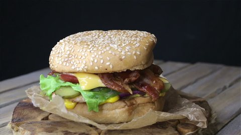 Chicken cheeseburger meal on a sesame seed bun topped with bacon. Rotation 360. Homemade food