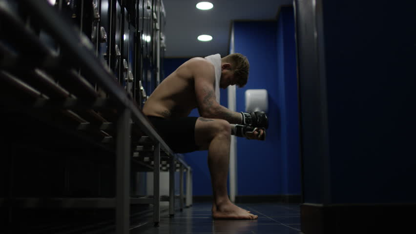 4K MMA fighter sits alone in locker room, psyching himself up before a fight UK - April, 2016