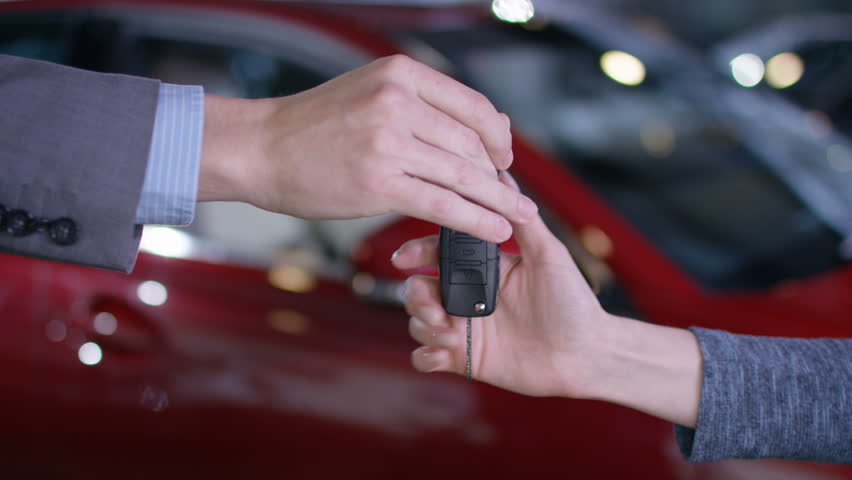 4K Close up on hands of salesman in car dealership giving key to new owner UK - April, 2016
