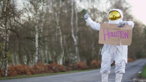 4K Astronaut returned to earth trying to hitch a ride from passing traffic. Shot on RED Epic. UK - April, 2016