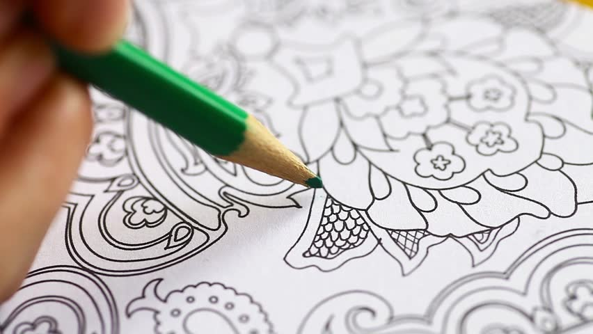Color video of a hand holding a pencil and coloring an adult coloring book.