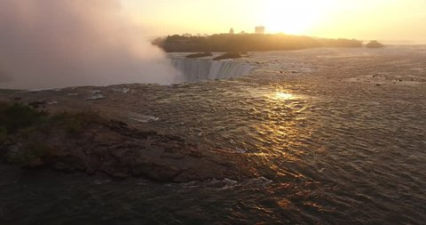 4K Aerial view of Niagara Falls. Flying towards the sunrise and falls.