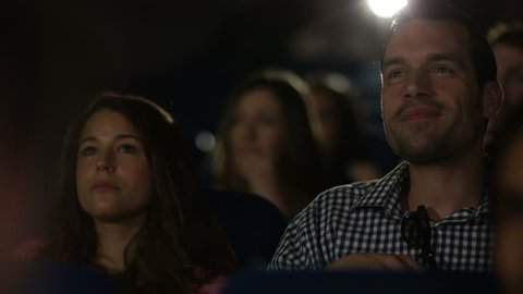 4K Man laughing loudly in cinema audience making his girlfriend embarrassed. Shot on RED Epic. UK - April, 2016