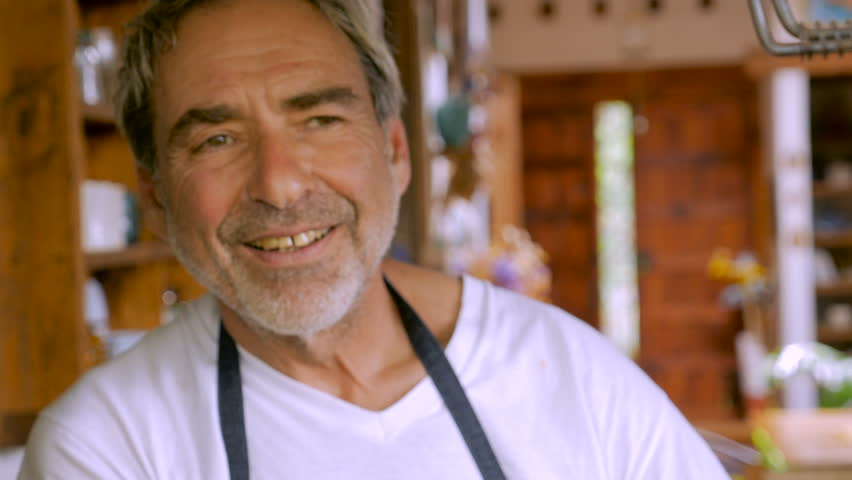 A smiling, attractive, happy, healthy, baby boomer man looks at the camera with a minor gap in between his teeth in his modern kitchen