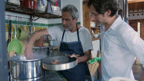 A father and son work together in a kitchen removing cooked liver and hard boiled eggs from a large pot in preparation for a Passover seder dinner.
