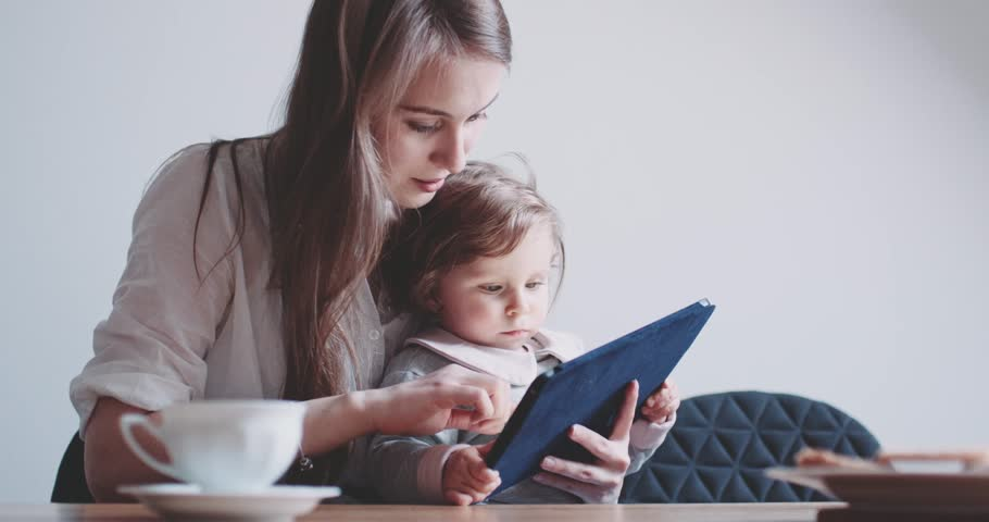 Young Caucasian Mother using Tablet with her Baby Daughter. Slow Motion 120 fps 4K DCi. Mother showing her Child digital Tablet. Children and Technology concept. Toddler girl. Cinematic family | Shutterstock HD Video #17076157