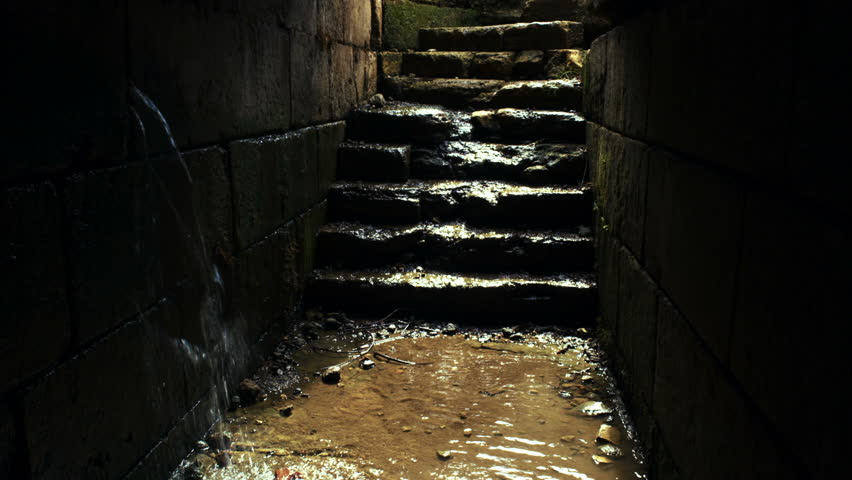 rain water pouring in from a crack in the rock walls and water flowing down the steps at the Palace of Agrippa in Banias, Golan Heights, Israel.