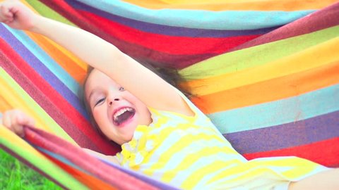 Happy little girl having fun outdoors, swinging in colorful hammock, summertime joy on sunny backyard. Smiling child. Slow motion 240 fps, full HD 1080p video footage