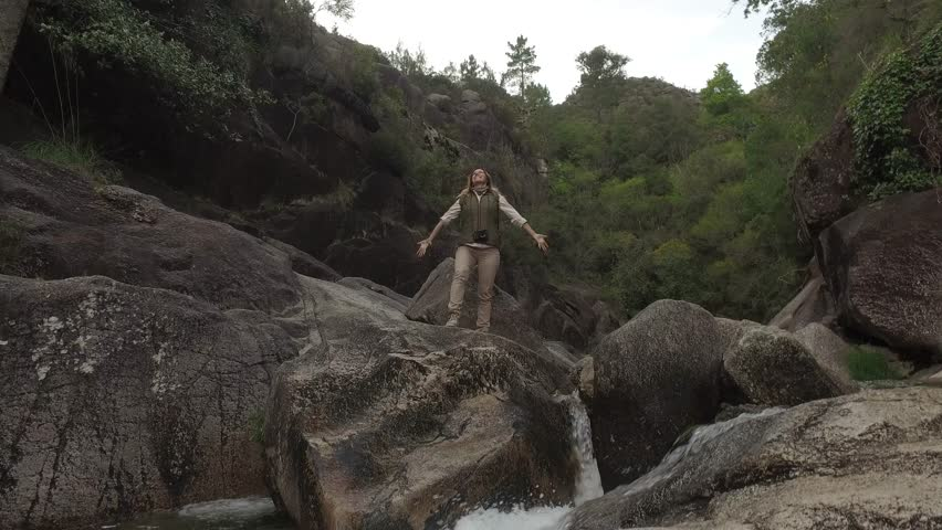 Woman hiker with backpack raising hands on the top of waterfall in 4k UHD video. Nº03   Shutterstock HD Video #17125699