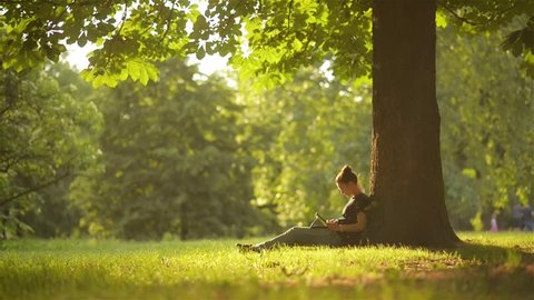 Young woman student using digital tablet for studying while sitting in the park, beautiful girl using tablet outdoors, beautiful garden, technology