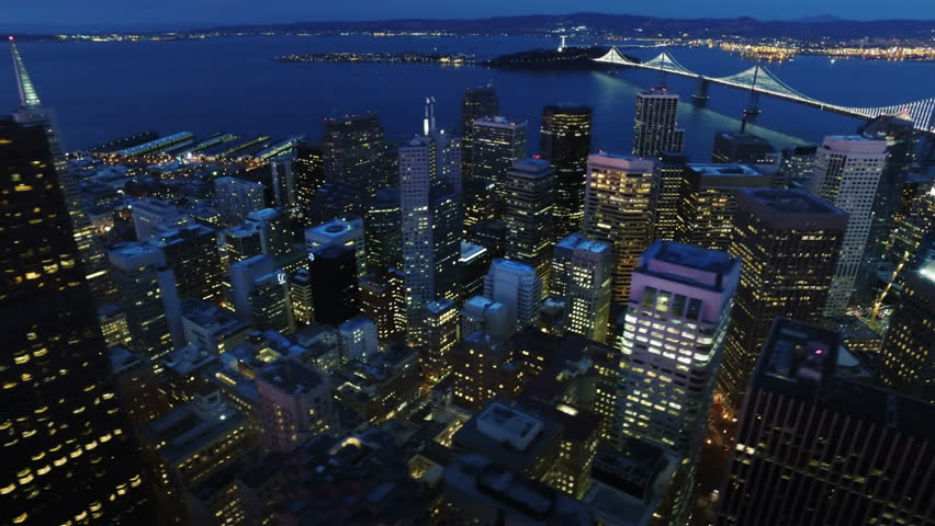 Aerial view of San francisco financial district and the Bay Bridge at sunset. California, United States. Shot from helicopter