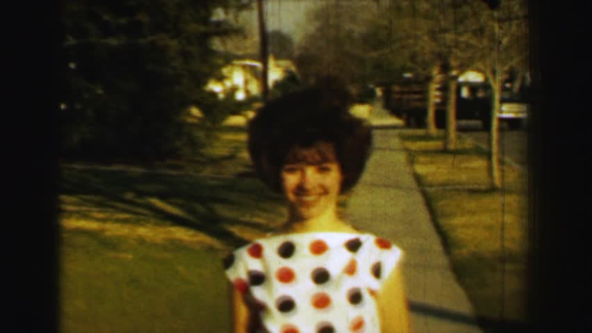 ST. LOUIS, MISSOURI 1958: Teenage girl curly perm hair polka dot blouse small orange shorts.