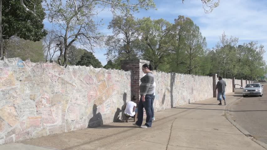 MEMPHIS, TENNESSEE - APRIL 09, 2016: Elvis Presley Mansion Wall in Graceland, Memphis. Family and childrens are looking into the wall