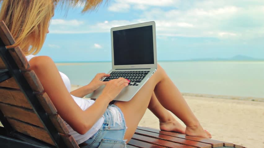 Young woman sitting at the sunbed with a laptop in front of sunset view. Lady freelancer working at the beach. | Shutterstock HD Video #17155357