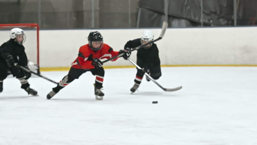 Young boys playing hockey on ice rink: one of them handling puck and his opponent chasing him and trying to get the puck in slow motion. Filmed with Sony Nex 700 | Shutterstock HD Video #17169319