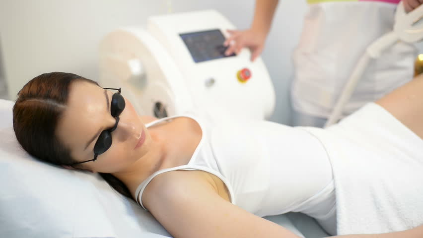 Beautiful woman getting permanent laser hair removal at beauty salon