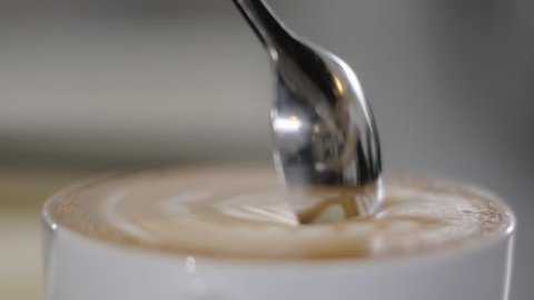 Cup of Coffee. Stirring with spoon. Close up of a beautiful coffee. Stirring with spoon.