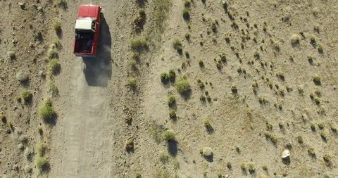 Aerial top scene of off road car in a dirt road on a desertic, dry, rocky, sand landscape. Camera follows the automobile. Piedra parada, chubut, Patagonia, Argentina.