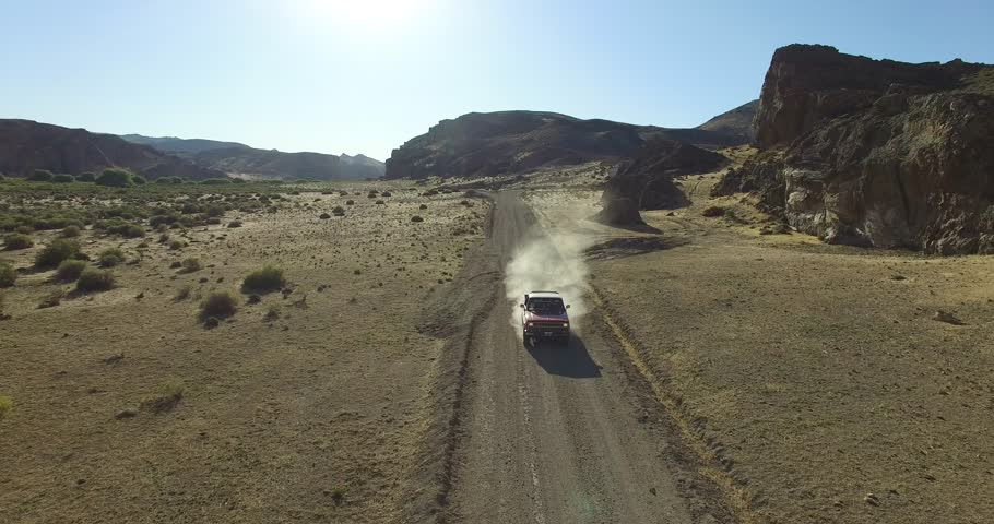 Aerial scene of car traveling on dirt road a dry, rocky, landscape. Monumental scenery. Car leves dust while driving. Canyon of Piedra Parada, Chubut, Patagonia Argentina. Hiking place.   | Shutterstock HD Video #17238289