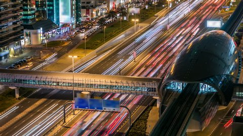 Metro Station with traffic on the highway night timelapse in Dubai, UAE. The Dubai Metro runs 40 km along Sheikh Zayed Rd, this armadillo like structure is a spectacular and futuristic design.