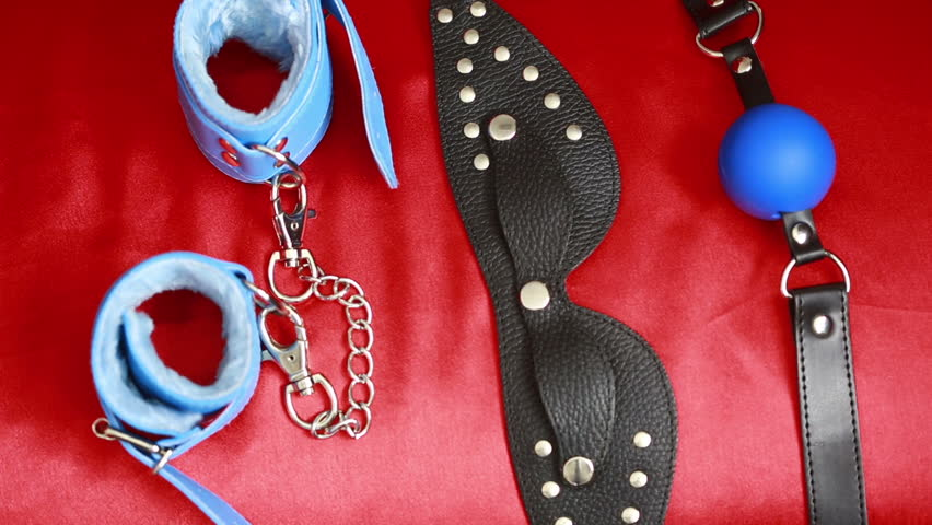 Leather accessories sex. female hand takes sex toy. mask, handcuffs and a gag