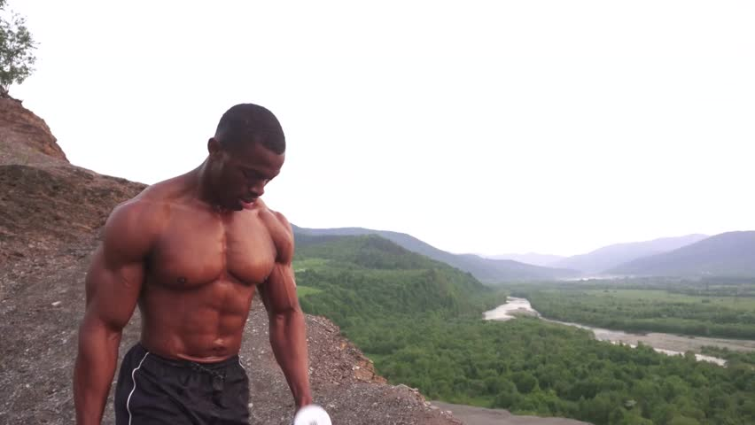 9b5e4a9eb7 Black african american muscular man lifting dumbbells against the cloudy  sky background in mountains