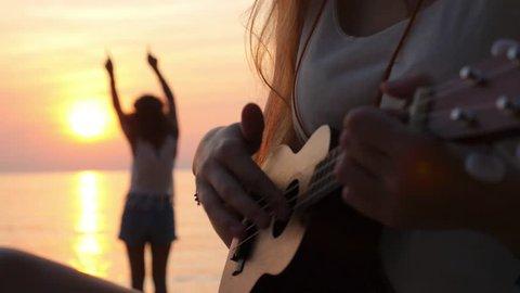 Hippie Girls Playing Ukulele Guitar and Dancing at Sunset