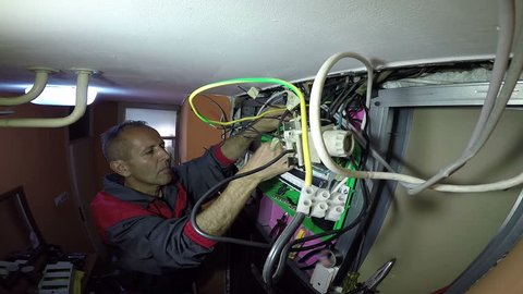 Electrician Whit Electrical Cables and Wires / Electrician builder engineer at work with electric cable wiring of fuse switch box HD1080p