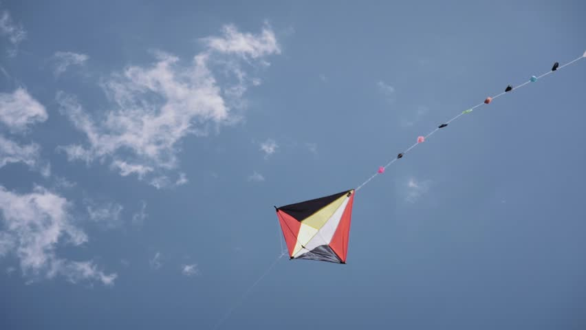 Colorful kite flying in sunny summer blue sky. Toy for children fun, leisure activity, recreation. Slow motion, slow-motion, slowmo, slowmotion. Copy space