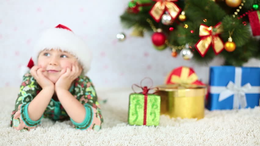Smiling girl in Santa hat lying near the Christmas Tree