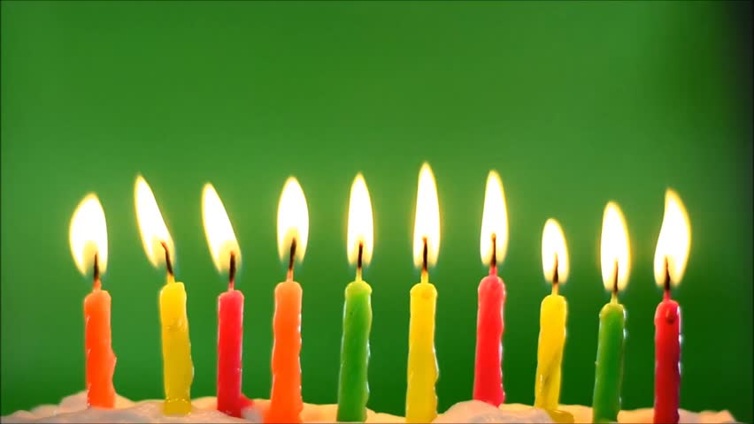 Ten Multi Colored Birthday Candles In White Icing Front Of A Green Background Flickering