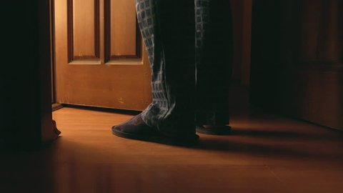 Adult man walks to a bathroom at the night and opens the door