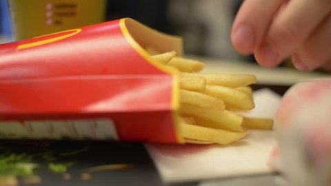 KHERSON, UKRAINE - MAY 19, 2016: Man eats French fries at McDonald's cafe table