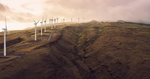 Aerial view of windmills turning at sunset, wind power turbines generating clean renewable energy