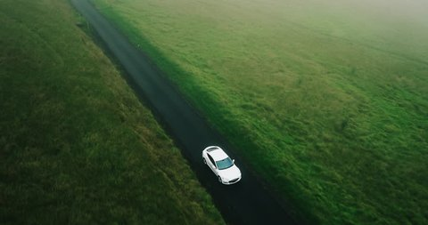 Aerial view electric car driving on country road, luxury car driving through mist at dusk with headlights