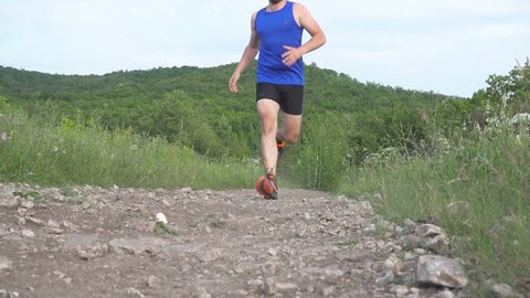 Slow motion. Man run on camera. Male runner exercising and training outdoors in nature. traill-running.