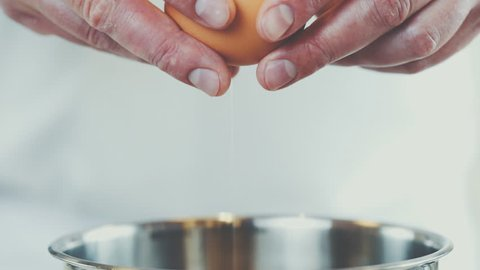 chef cracking an egg in a bowl