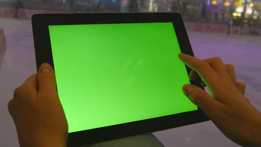 Female hands using tablet pc with green screen in shopping mall. Lot of people skate on indoor ice rink at the background #17379259