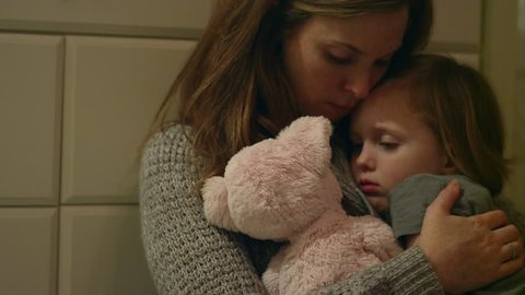 Sad, scared young girl with a stuffed animal being held by her mother in her room