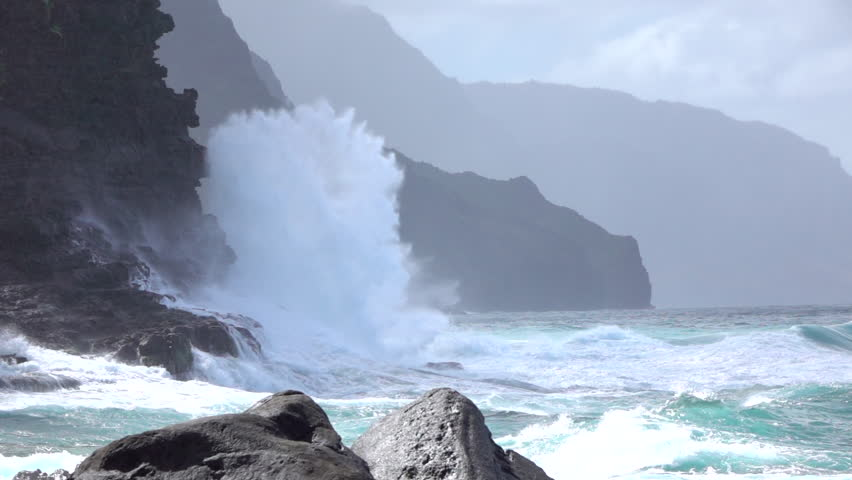 SLOW MOTION: Dramatic powerful ocean wave uprising from the restless emerald sea, splashing and crushing into majestic crag ocean cliff. Unstoppable ocean weaves spewing salty spray against rocky wall