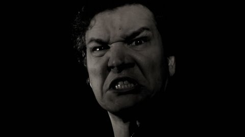 Man scary screaming expression. A monster of a man scares with a loud scream in film noir black and white. Rage faced man yells in anger.