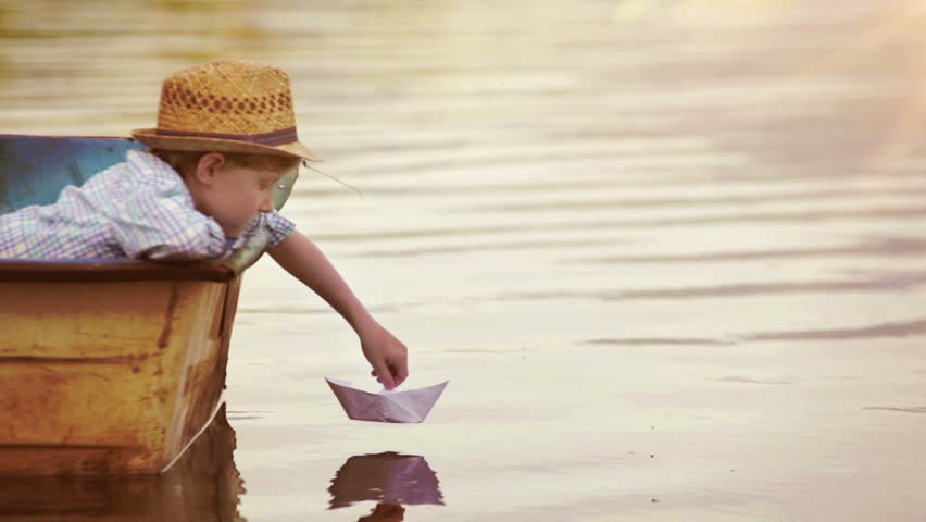Boy places a paper boat on the water's surface and blows for it to sail away | Shutterstock HD Video #17437375