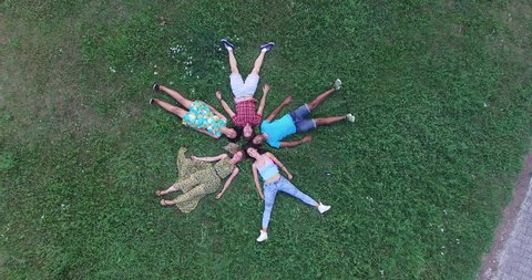 Aerial view of five happy friends forming a star shape lying in grass
