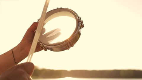 Playing a musical instrument tambourine on background sky at sunset