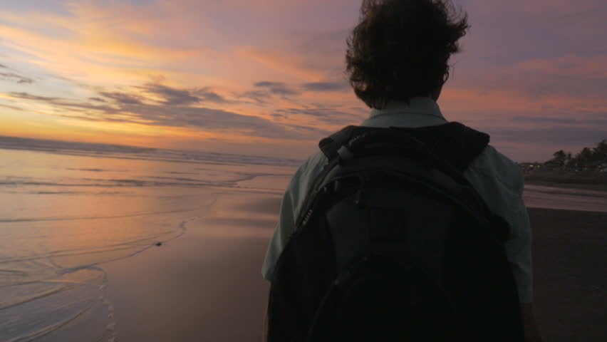 A middle aged man walks with a backpack on along the beach during a magical sunset in slow motion