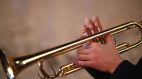Hands of man pushing button and holding on brazen trumpet close up.