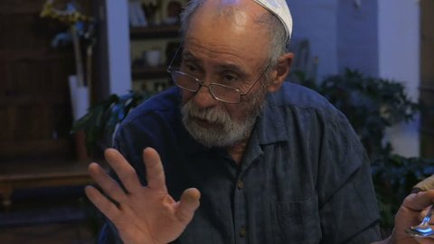 An older man explains a jewish tradition at a passover seder after he passes a small dog from his lap to someone else.