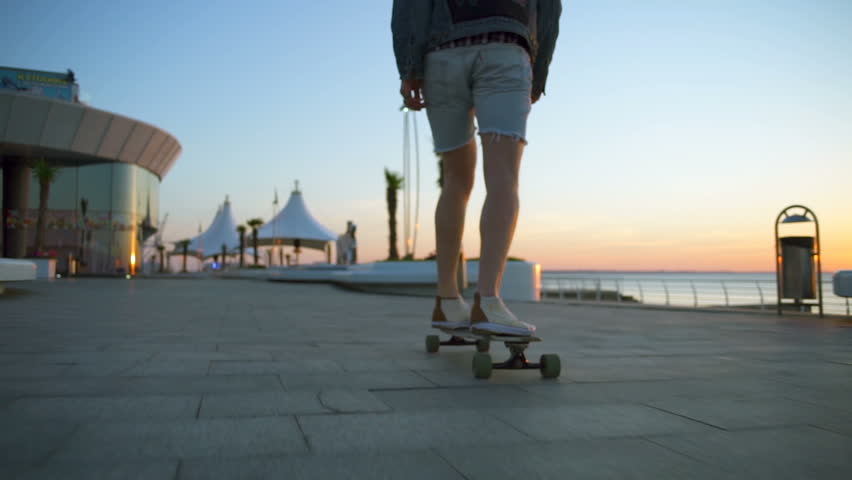 close up male legs on longboard moving by seafront slow motion #17517379