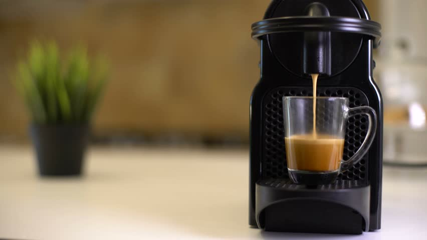 Automatic coffee machine or coffeemaker pouring espresso coffee at home in a glass cup. #17523859