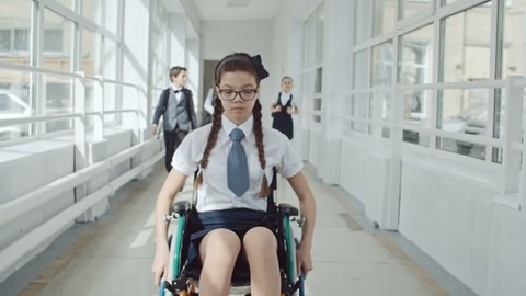 Disabled girl riding wheelchair at school while her friends running through corridor to help her